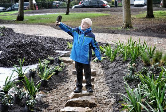 Boy holding spade inside a rain garden