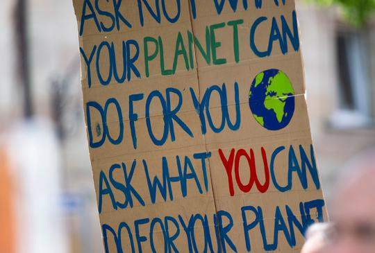 Youth climate activist with sign at a protest